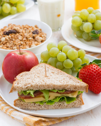 Cute baby 1 years old sitting on high children chair and eating fruits alone in white kitchen.