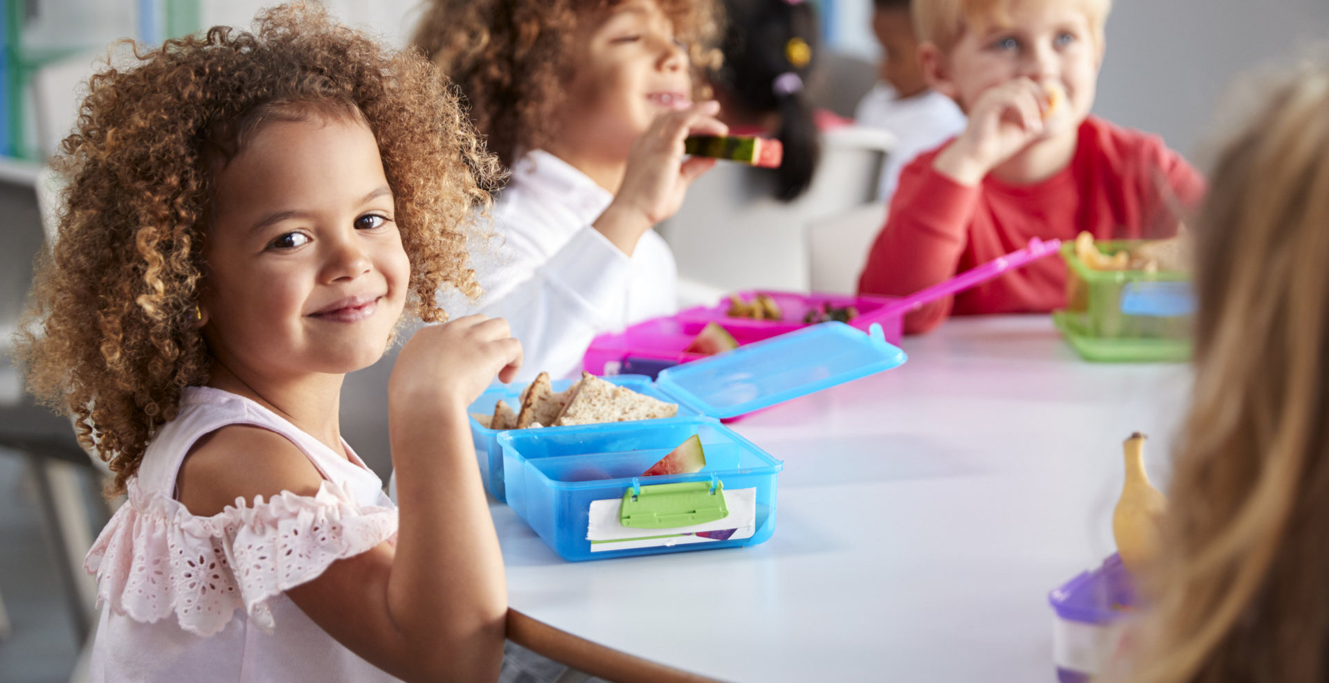 Close up of smiling young children sitting at a table eating their packed lunches together at infant school, girl smiling to camer.