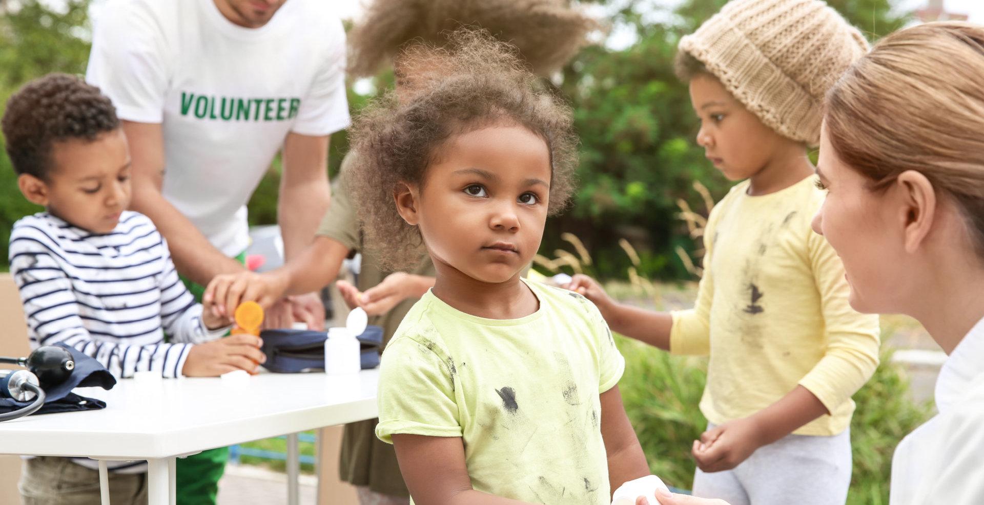 Volunteers giving vitamin tablets to poor African children outdoors