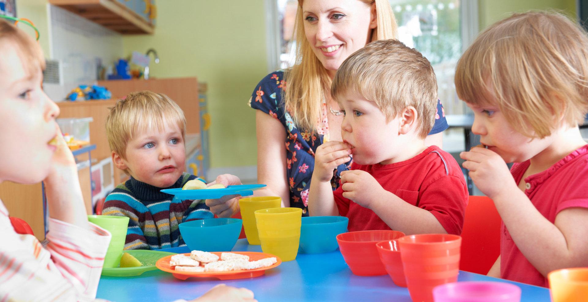 Teacher With Pre School Children Eating Healthy Snacks At Breakt.