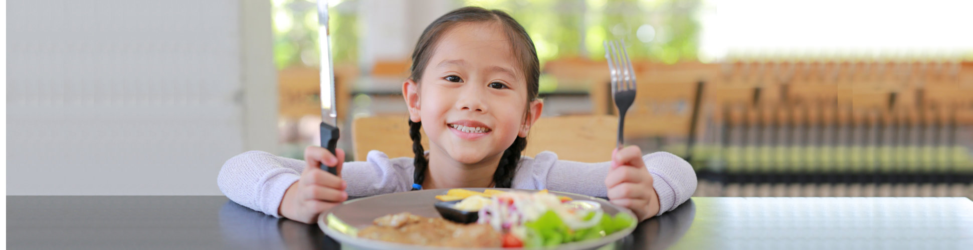kid smiling while holding cutlery