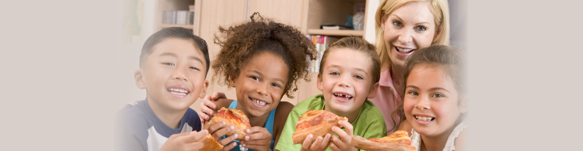 kids smiling while holding pizza